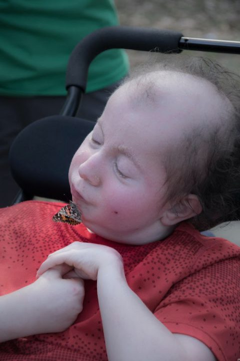 child in wheelchair kissing a butterfly